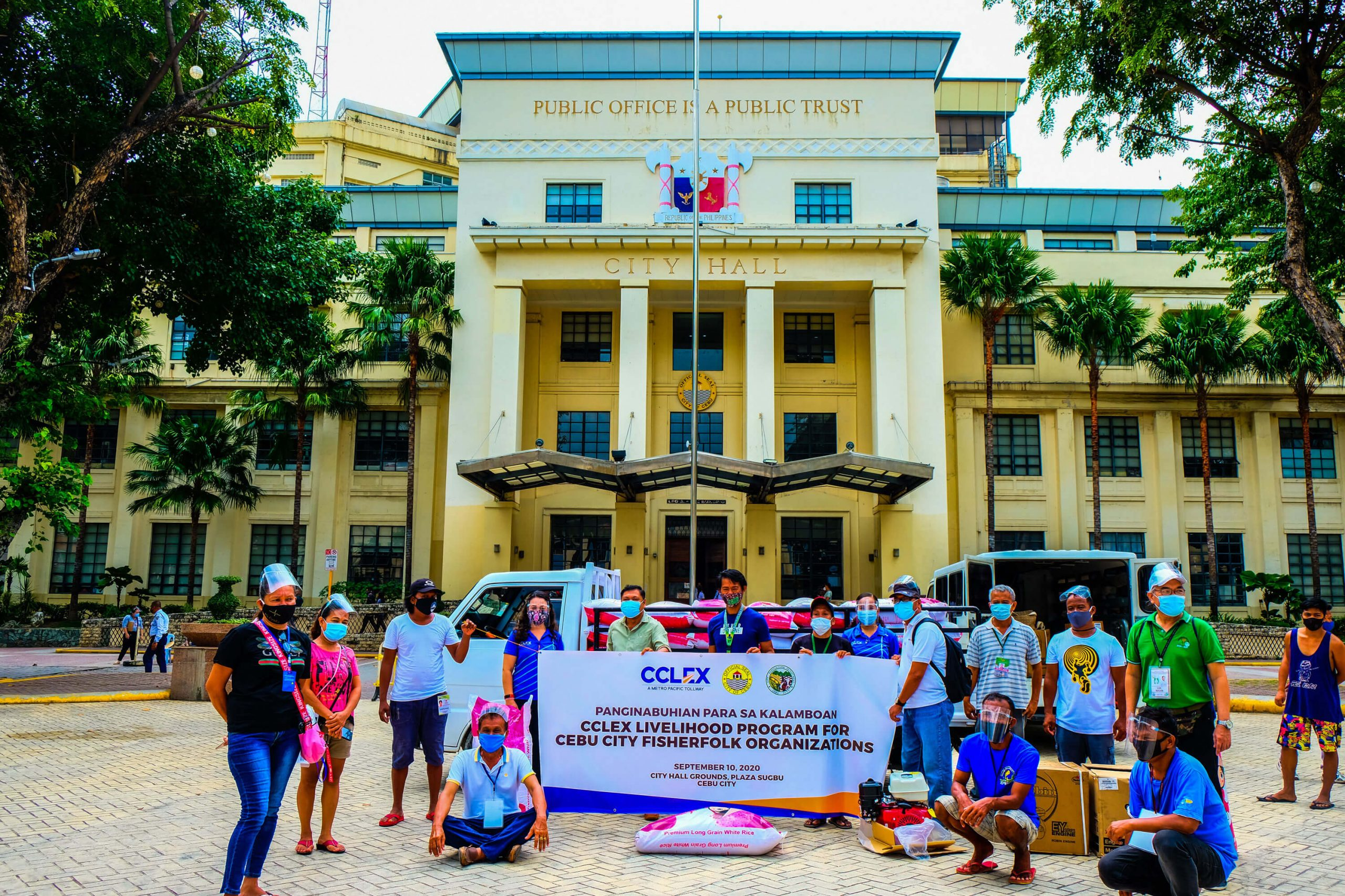 "ASSISTANCE. The Cebu Cordova Link Expressway Corporation turns over sacks of rice for their ""Bigasan ng Bayan"" and marine engines to officers of the fishermen groups."